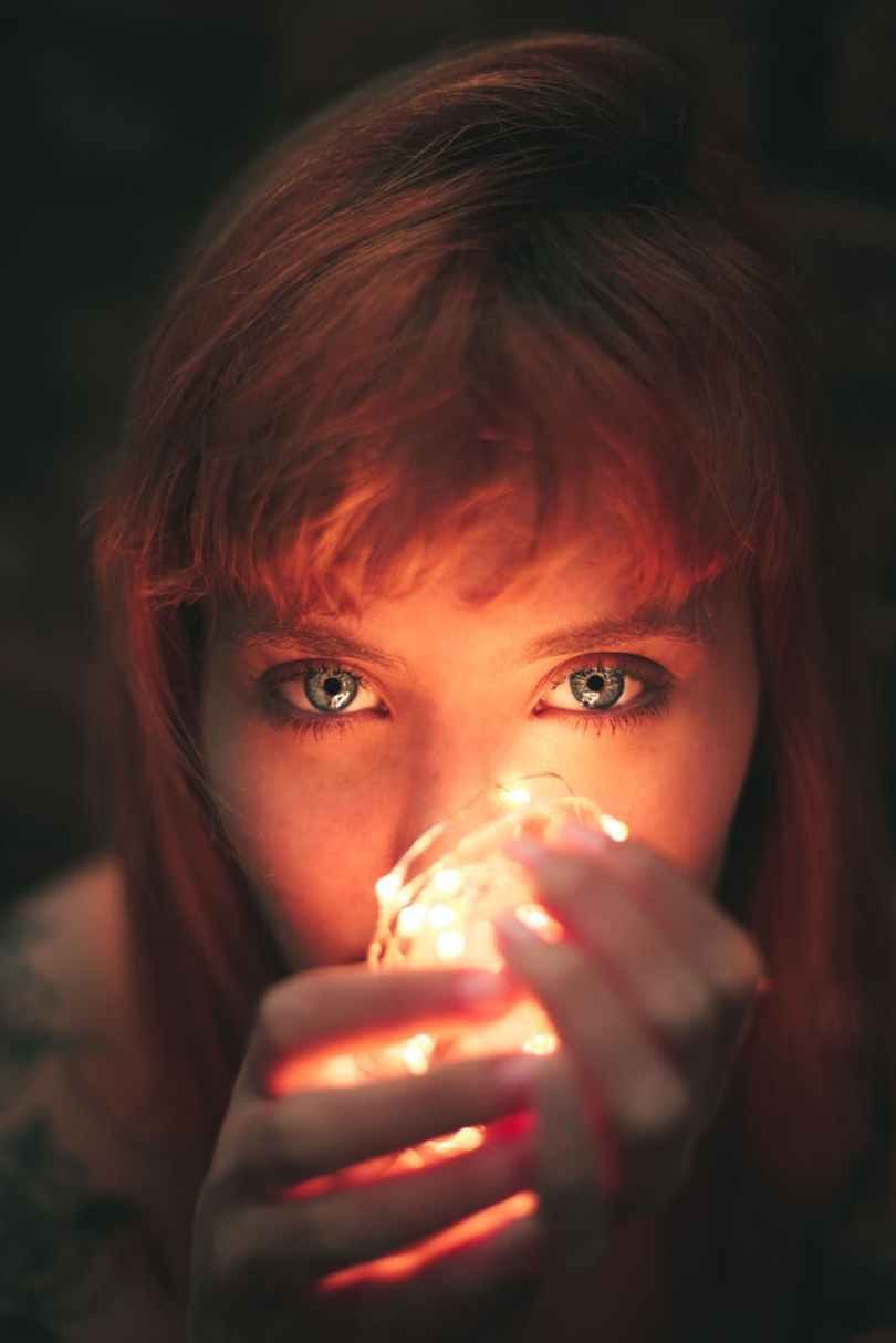 close up photography of woman holding string lights